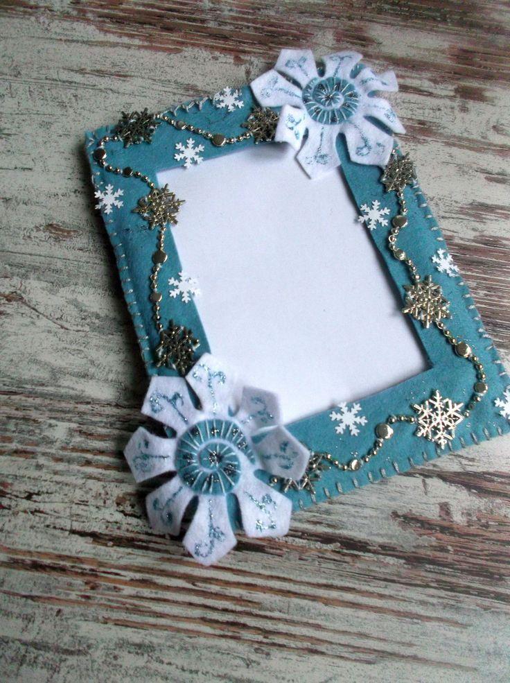 Rámeček Zimní vločka.. Origo ručně šitý filcový rámeček.. Ozdobte si interiér filcovým rámečkem na postavení - zavěšení. Celý ručně vyrobený. Materiál - filc, zpevněno tvrdým kartónem. Ozdobeno našitými aplikacemi vloček - plast, karton, domalovaných glitry. Velikost rámečku je cca 20x15 cm, vnitřní rozměr je 9 x 13 cm. Odpovídá klasické malé fotce. Na ...