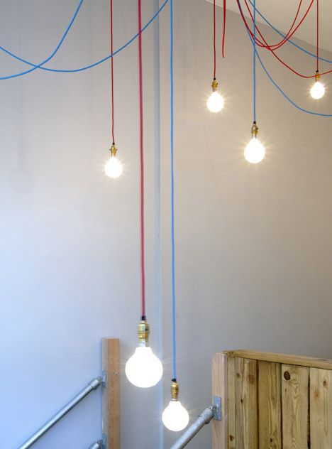 DIY affordable designer lightning: a web of red and blue cables with large globe light bulbs