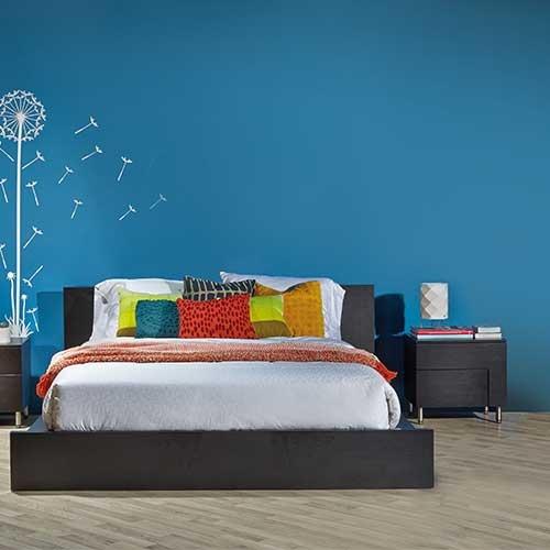 La cama y la mesa auxiliar negra, se complementan muy bien con el blanco y los colores vivos. Es sobria sin dejas de verse jovial.