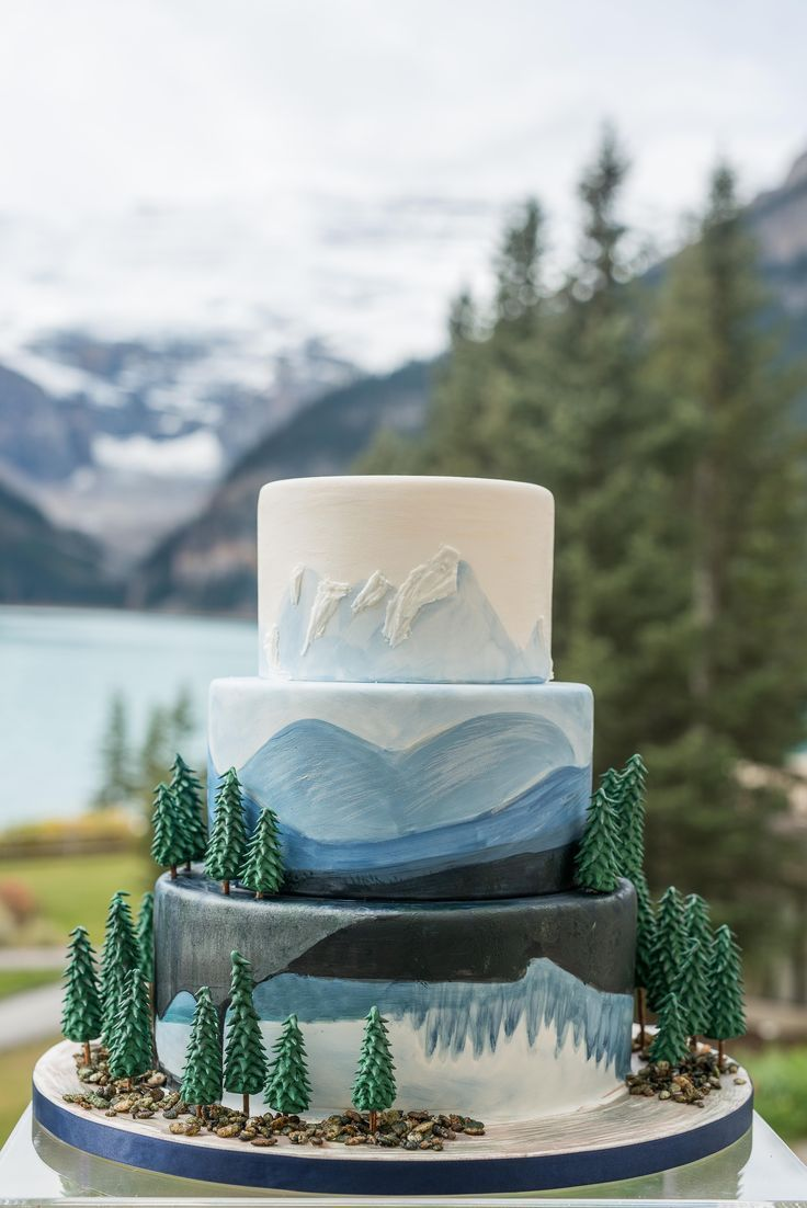 Fun, nature inspired watercolor cake with trees and blue hand painted mountains at Lake Louise.