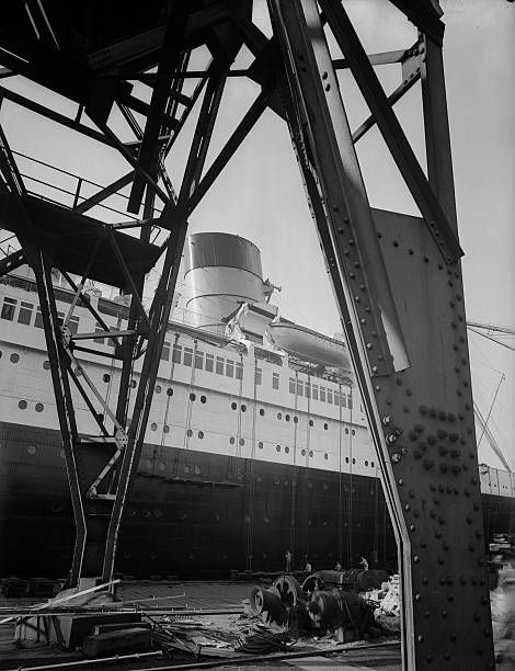 The great transatlantic passenger liner SS Queen Mary nears completion at a shipyard on Clydebank, Scotland. Measuring 1,020 feet in length, with a gross tonnage of 81,237, the Queen Mary won the Blue Riband for the fastest crossing of the North Atlantic in 1938. She was withdrawn from service in 1967, and is currently moored at Long Beach, California.
