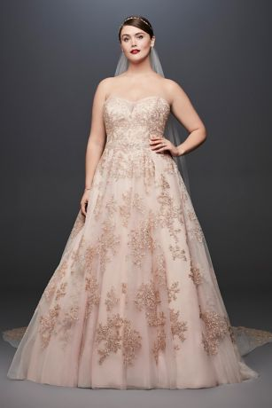 Metallic appliques lend this illusion-bodice plus-size A-line gown a soft glow. …