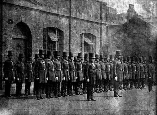 Manchester City Police peelers parade in the yard of the city's Albert Street Police Staion in the 1850s. Early police officers wore top hats and frock coats to allay public fears that the new forces were part of the military. To find out more about Greater Manchester Police please visit our website. http://www.gmpmuseum.com