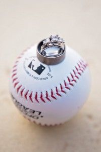 A classic wedding ring shot-the wedding and engagement rings on a baseball #Phillieswedding #baseballweddings #engagementshoot