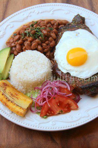 Bistec asado con huevo, menestra, arroz y platanos