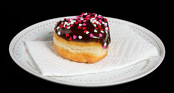 A photo of a homemade Boston Cream Donut, heart-shaped and dusted with red, white and pink sprinkles.