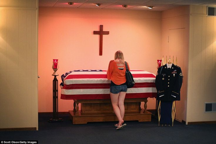 Jackie Rozek spends a moment with the body of her boyfriend, U.S. Army Pfc.Aaron Toppen, ...