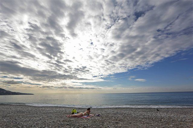 A woman sunbathes as she takes advantage of warm autumn weather temperatures on the beach in Nice October 1, 2014. (Photo by Eric Gaillard/Reuters)