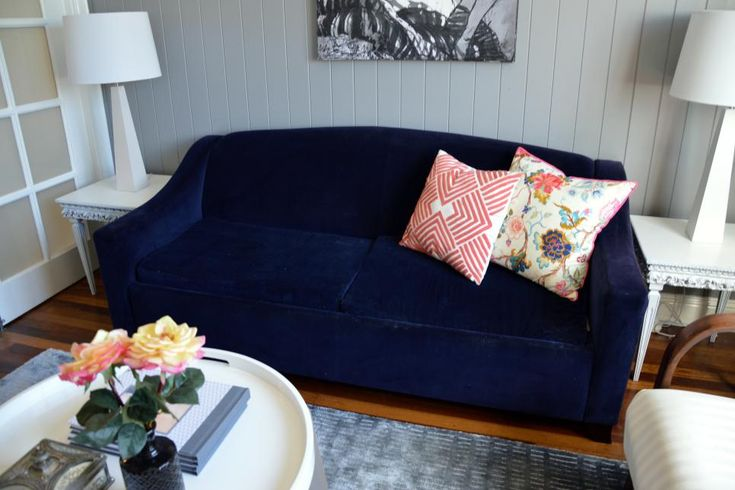 With soft gray walls and fun splashes of color, this small living room is cozy yet sophisticated. A stylish velvet sofa lends depth to the room with its deep navy hue.