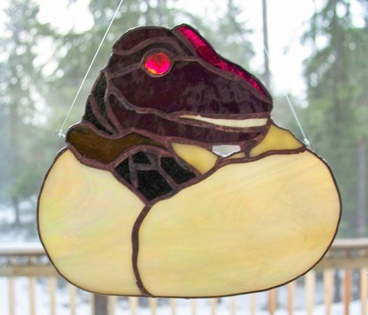 Stained glass suncatcher of a egg of baby T-Rex dinosaur