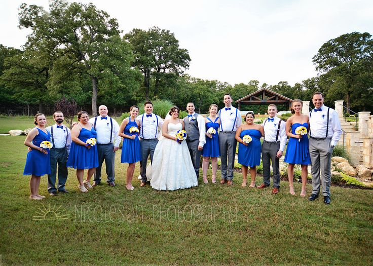 Royal blue bridal party (bridesmaids in royal blue short dresses with sunflower bouquets, groomsmen in white shirts, grey pants, a royal blue bow tie, and suspenders).  Taken at THE SPRINGS in Denton (The Ranch) by Nicolesun Photography.