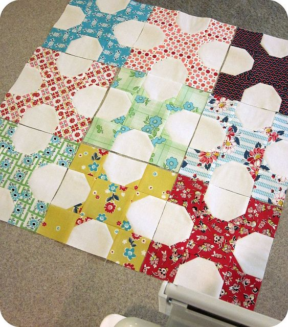 """Pinner said: Great block.  (No pattern) So cute. I see it's a 9-patch. If I were to use 5x5 charms, I'd cut a colored charm into 4 pieces vertically and horizontally to make 4 2.5"""" blocks. Then take a white square and sew two of the little squares diagonally in 2 corners."""