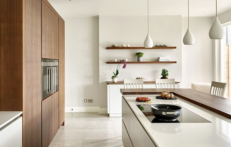 Modern kitchen design in Walnut & Cornforth White. Split level Island with adjoining breakfast bar and integrated hob. Tear drop pendant island lighting. Wall cabinets in American black walnut with wall-mounted double oven.