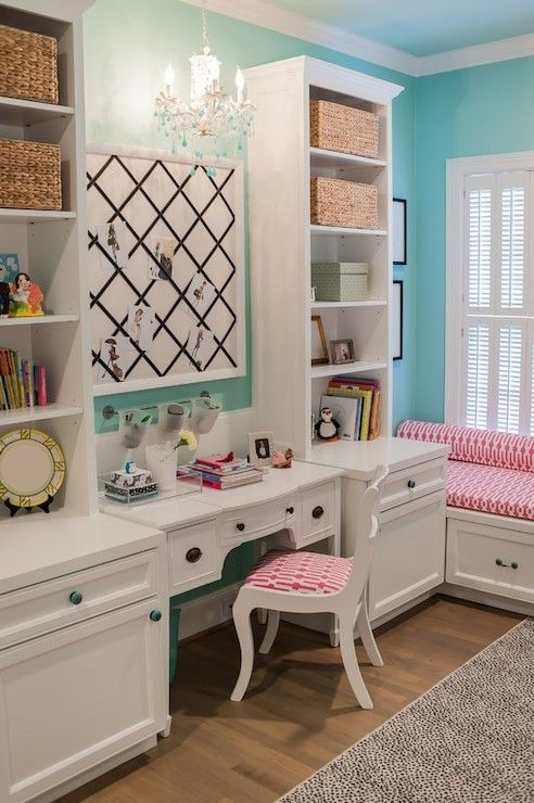 Janet Gust Interiors - Sweet girl's room with built-in cabinets and bookcases flanking a white bow front desk lined with a white chair with pink geometric seat below a black ribbon trimmed memo board illuminated by a white and turquoise beaded chandelier. The bedroom features a built-in window seat topped with a pink and white geometric seat cushion framed by turquoise walls over hardwood floors layered with a beige and black dotted rug.