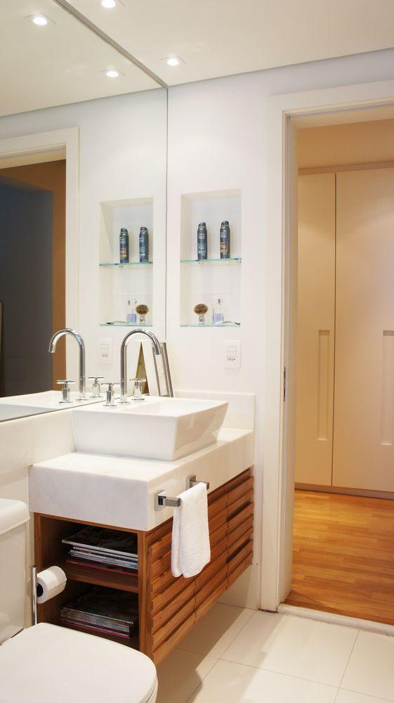 Banheiro com bancada branca e gabinete com nicho lateral.
