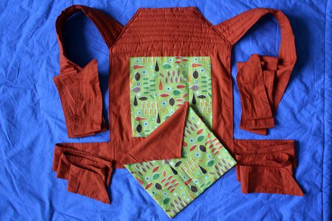 This handmade Mei Tai is a traditional, Asian-inspired baby and toddler carrier. The main (blue) part is made of a strong organic cotton.  It offers 4 long straps that are tied around the mother's body in various different ways allowing you to carry your baby on the front and back, and they are...