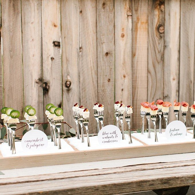 An array of paired cheeses served on standing silver forks, styled by The TomKat Studio for Real California Milk.