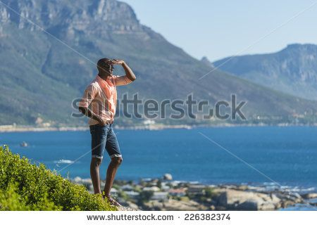 http://www.shutterstock.com/pic-226382374/stock-photo-african-black-man-standing-on-a-high-rock-overlooking-cape-town-as-he-points-and-scouts-the-blue.html?src=WuffEuvvGWj02MQSGcnIHQ-1-21 African Black Man, Standing On A High Rock Overlooking Cape Town As He Points And Scouts The Blue Sky, Ocean And Mountains On A Sunny Summers Day Stock Photo 226382374 : Shutterstock