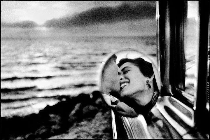 Photo: Elliott Erwitt: Couple kissing viewed in side mirror of car at beach sunset, 1955.