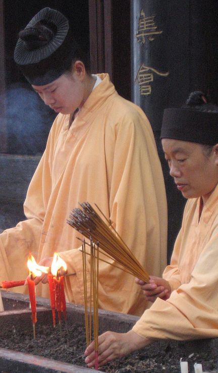 Female Daoshi, candles, and incense