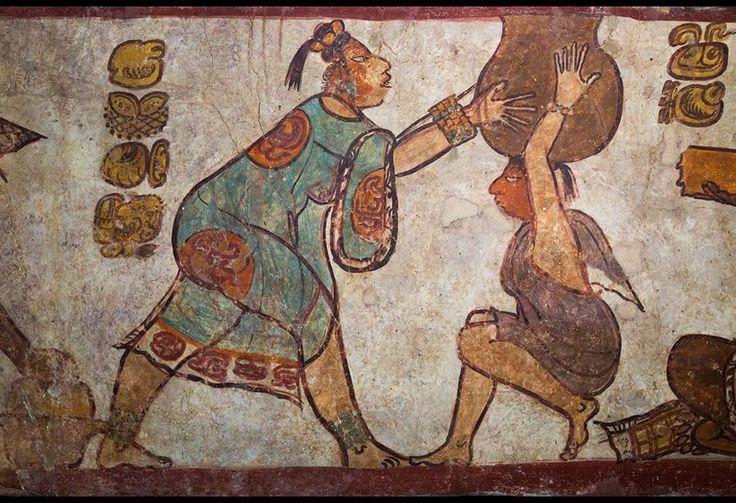 Scena dipinta su una parete di una piramide di Calakmul   al tempo dei signori del Serpente , nel VII secolo d.C, : una donna in un leggero abito azzurro aiuta un'altra a caricare sulla testa una pentola probabilmente piena di zuppa di mais.
