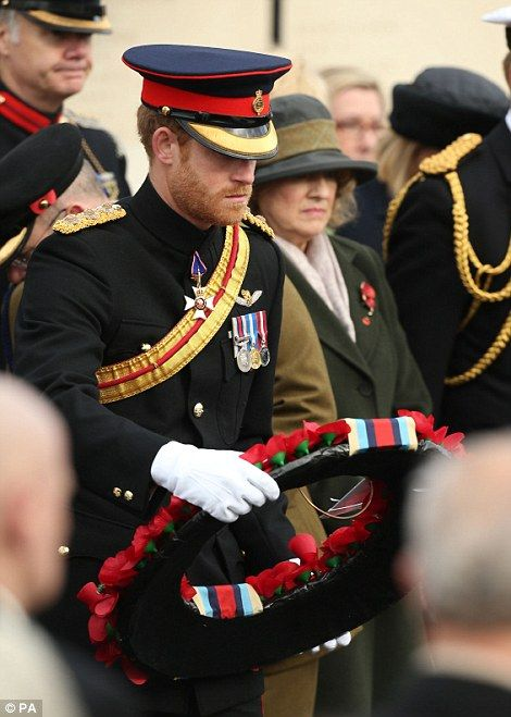 Prince Harry lays a wreath before he gave a reading during the service and inspected the names on the memorial's towering Portland Stone walls