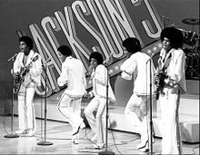 Jackson 5 (Jackson Five, sometimes 5ive) at concert microphones on stage. From 1964 - 1990, Jacksons played R&B, soul, pop, 1970s disco. 6-1/2 years in Motown. Sold 100 million records worldwide = one of best-selling music artists of all time.