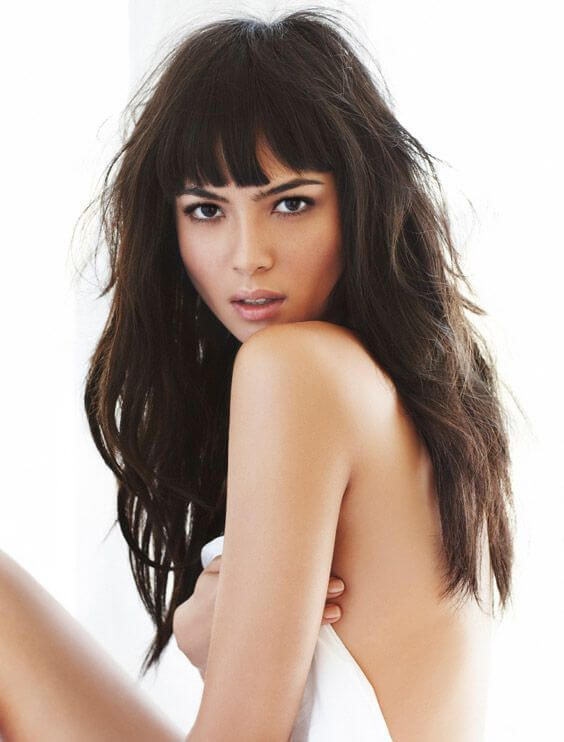If side bangs are not for you, consider blunt bangs instead. This brunette model has added straight-across bangs to her long, wavy shag haircut for a funky rocker look.