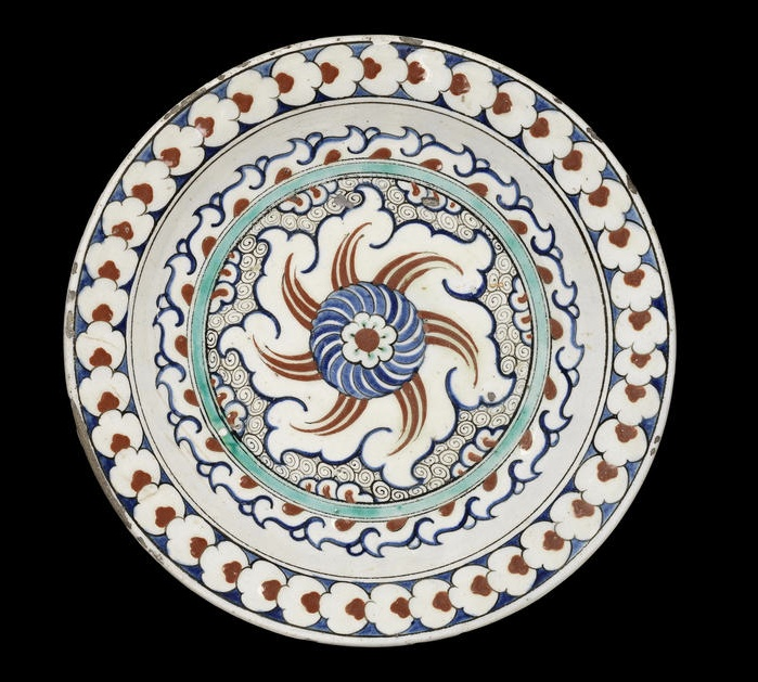 An Iznik polychrome pottery Bowl   Turkey, circa 1590  with sloping rim on a short foot, the white interior painted with fine black spiralling motifs around a concentric red and blue swirling flowerhead, within a plain turquoise band, the cavetto with blue, white and red scrolling leaves, in a blue border of overlapping red and white trefoils, the underside plain   30.6 cm. diam.