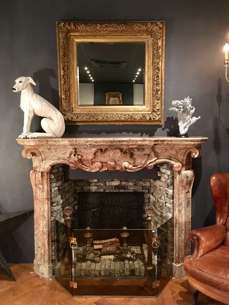 Rouge royal marble fireplace, antique, interior, sculpture dog, gold mirror, antique floorboards, old leather chair, coral, design, vintage