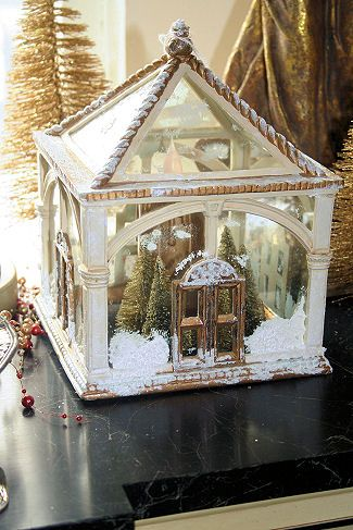 Little glass house embellished with snow, bottle brush trees, and a flicker light.