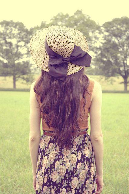 Sun hat with black bow, long, flowing curls, tan / brown top, black floral skirt, brown belt