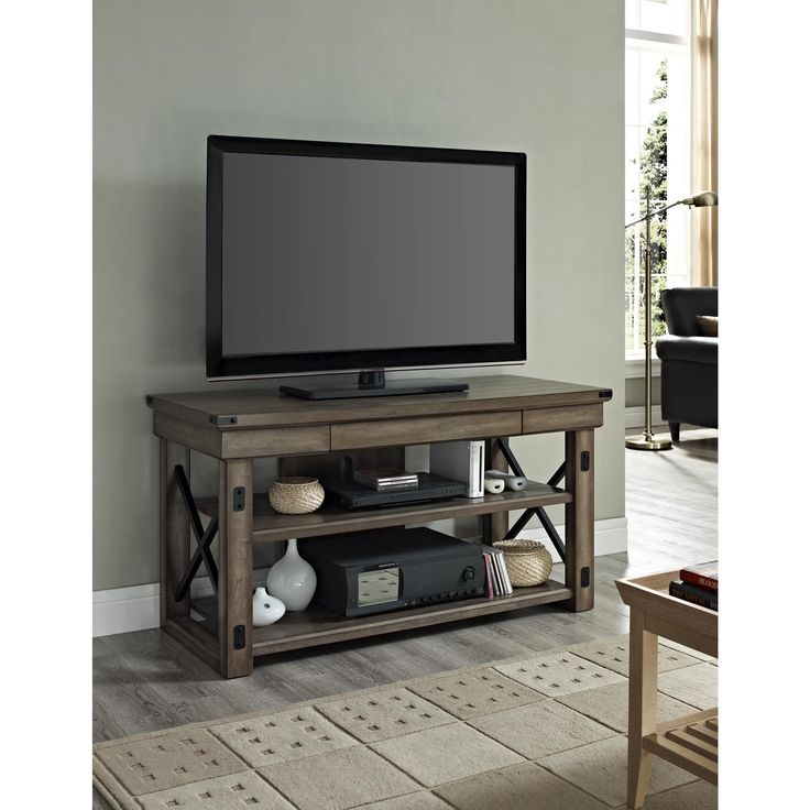 Rustic, yet contemporary, this handsome TV console from Altra makes an impact in any living room. Crafted with grey veneers, this piece features black metal side frames for support, allowing it to hold a TV up to 50 inches and 70 pounds.