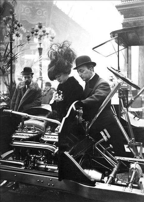 Jeune femme se faisant expliquer le fonctionnement d'un modèle au Salon de l'automobile de Paris, en 1908. © Maurice-Louis Branger / Roger-V...
