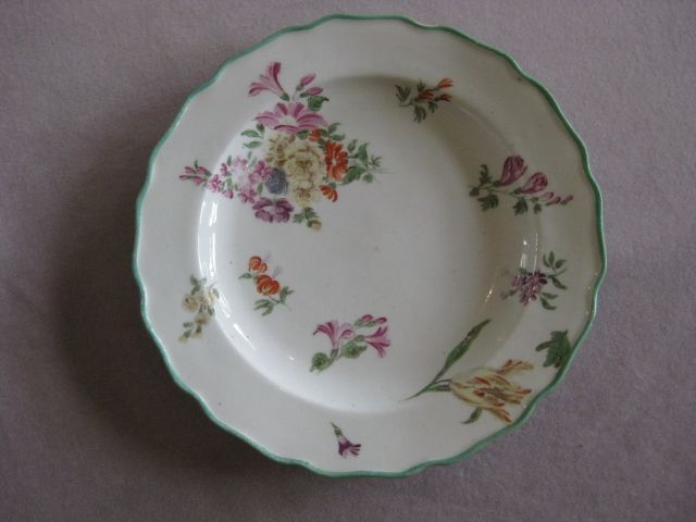 A Chelsea plate with a green painted, wavy edge and painted with sprays and sprigs of flowers.  Brown Anchor  Circa 1760 Width 8 1/2""