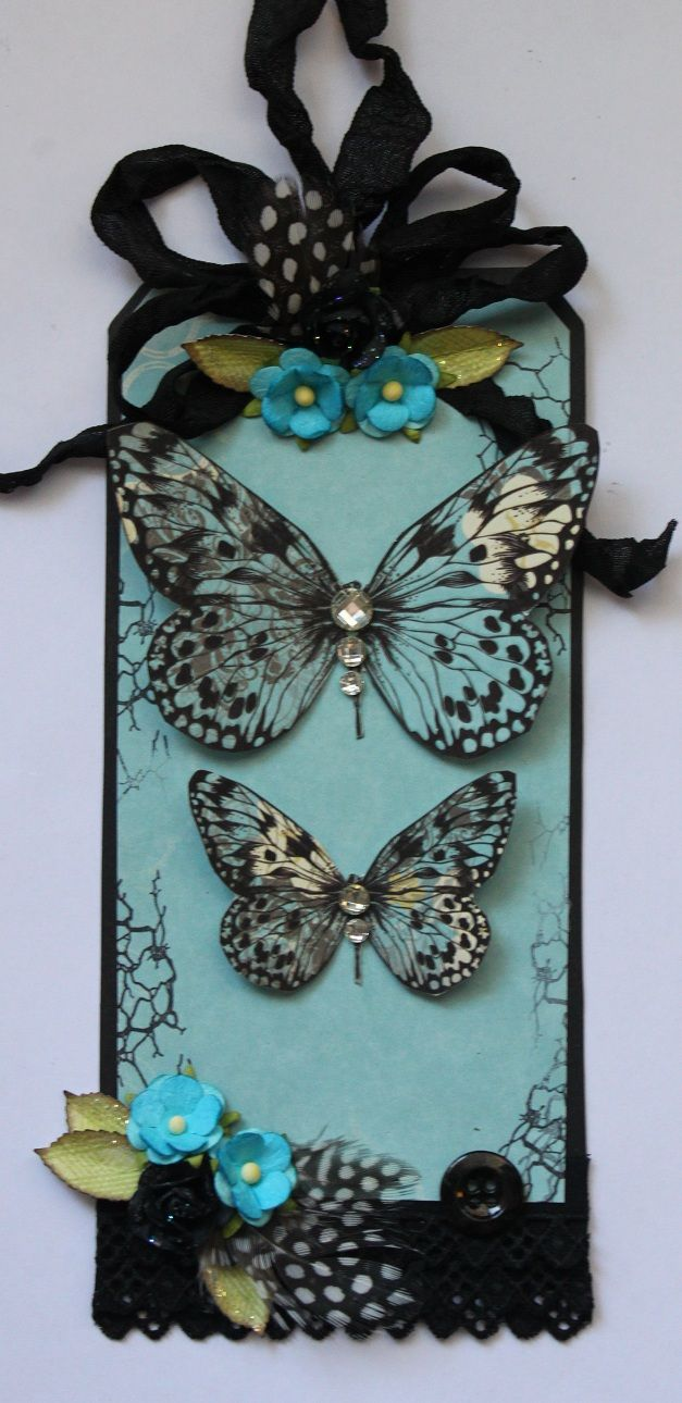 Tag: butterflies, feathers, paper flowers, ribbon, fiber, blue and black tones. Free - Scrapbook.com