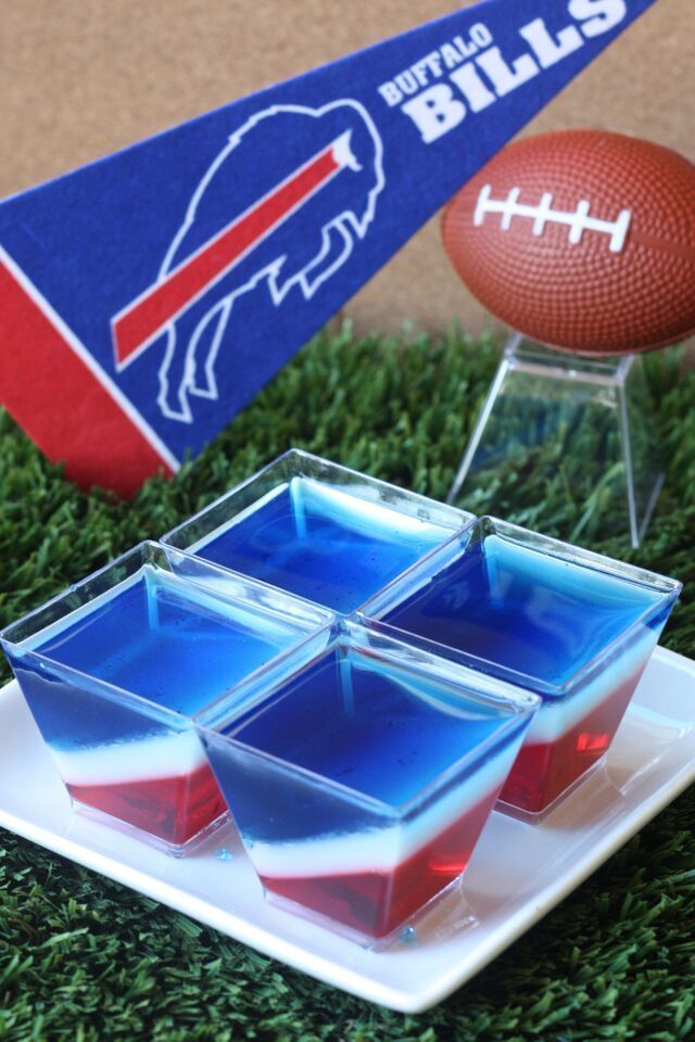 Buffalo Bills Jell-O Shots  (3 oz. box cherry Jell-O 3 envelopes Knox plain gelatin  2 1/2 cup vodka  1/2 cup milk 1/8 cup sugar 3 oz. box berry blue Jell-O Blue food coloring)