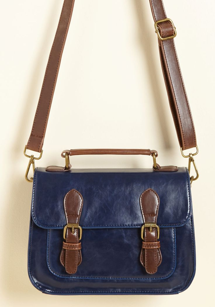 Midday date? Trek across town? This navy purse has your every wandering covered with its smooth, faux-leather fabric, brown accents, antiqued gold hardware, and timeless look. The better question is - what scenario can't this perfect purse handle?