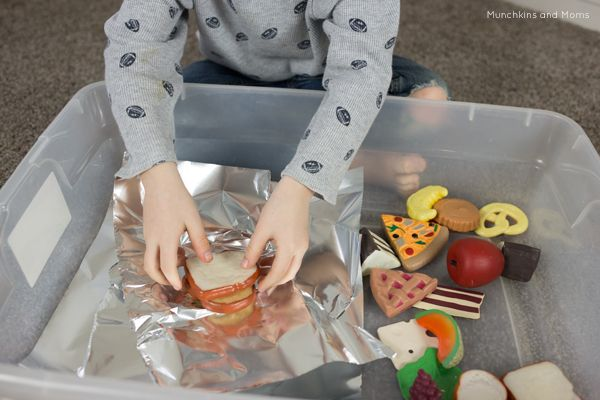 Play food and foil- this is great fine motor work for preschoolers! Great idea to add to the play kitchen as well.