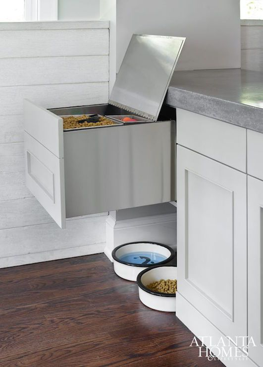 Kitchen boasts a small nook filled with pert food bowls tucked under a pull-out pet food storage drawer topped with thick concrete countertops.