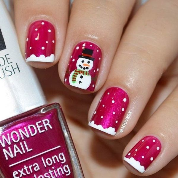 A cute and adorable snowman and polka dot winter themed nail art design. Paint a cute snowman on your nails amidst a magenta shade and white falling snow on a snow tipped nail.