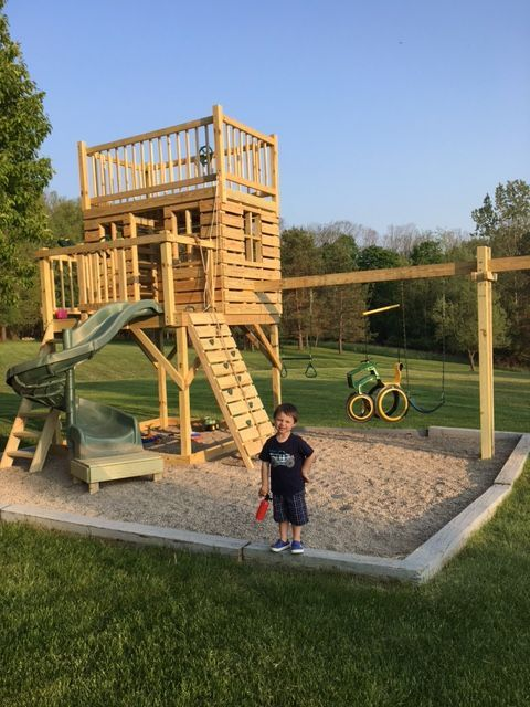 Boy Enjoying His New Three Level Clubhouse With A Slide Rock Wall
