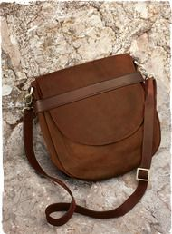 The equestrian-style saddle bag in weathered brown leather is outfitted with an adjustable shoulder strap, pockets and a front flap with magnetic snap closure.