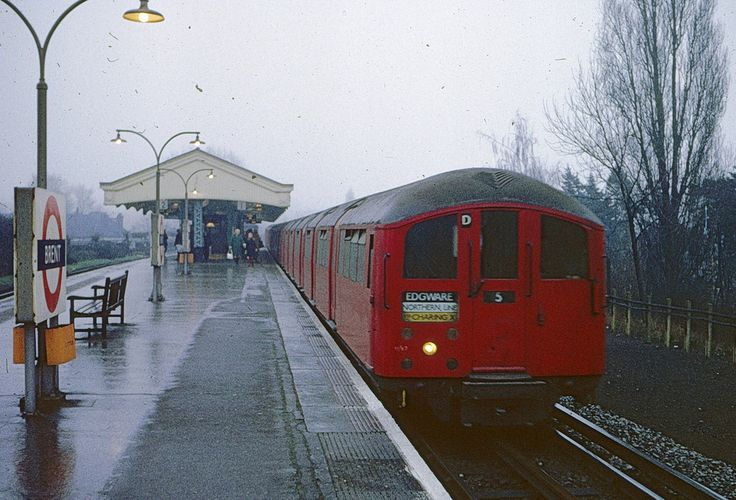 Brent Station, 1973. __ On a wet January day, a train of 1938 tube stock bound for Edgware calls at Brent (not yet named Brent Cross). The space to the right of the track is the site of one of the passing loops at this station used from 1927 to 1936 to allow one train for London in the morning and one from London in the evening to overtake a stopping train here.