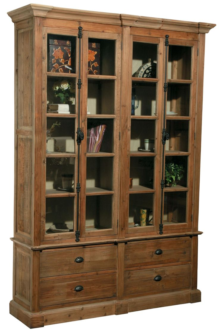 This bookcase is made of reclaimed pine and has a wonderful warm tone. This piece has four glass doors on top, exposing four shelves behind each set of two. Below, there are four drawers, perfect for stowing away anything from blankets, silverware, and books. This bookcase has beautiful crown moulding, exposed wood grain, and an antique-looking metal locking mechanism. Place this item in your dining room to use as a curio cabinet or put it in your living room or home office.