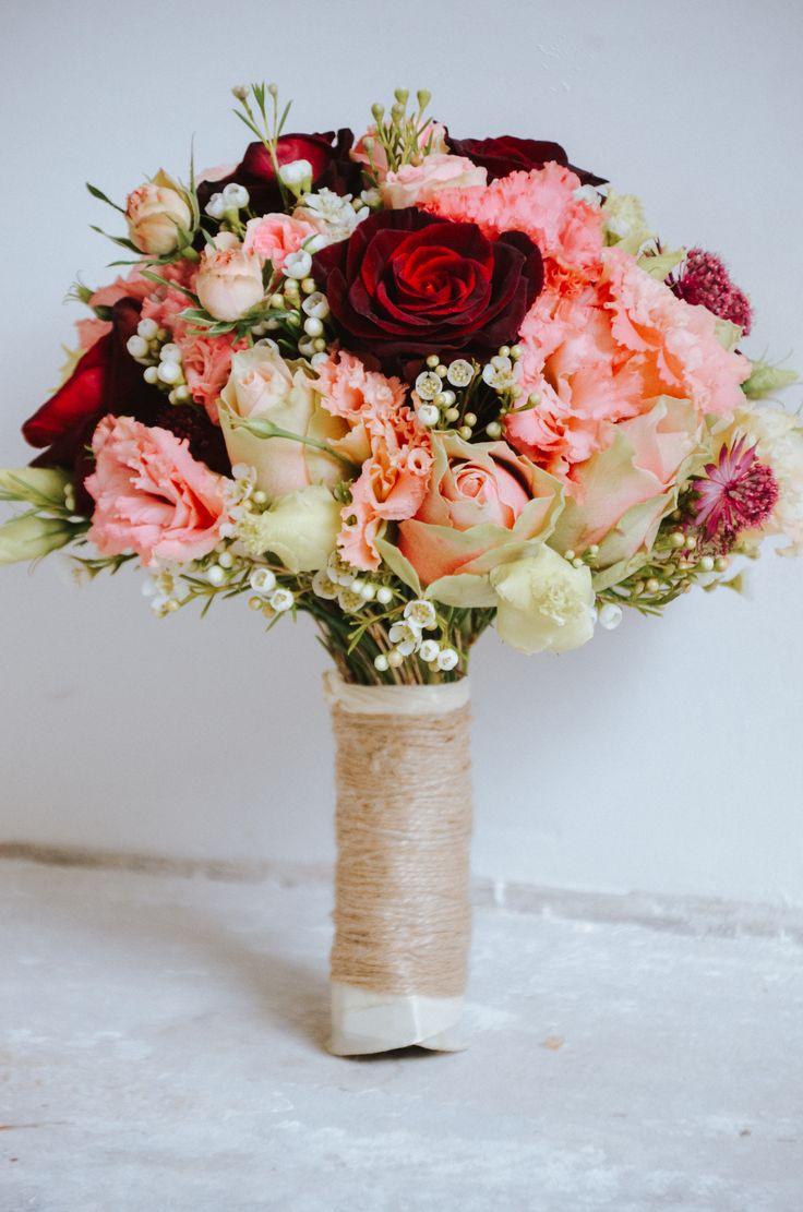 Ein Brautstrauß mit roten Rosen (alias Black Baccara), La Belle, Wachsblume, Lysiantus. Alles fest am Stiel zusammengebunden und durch Seidenband und Jute verstärkt.