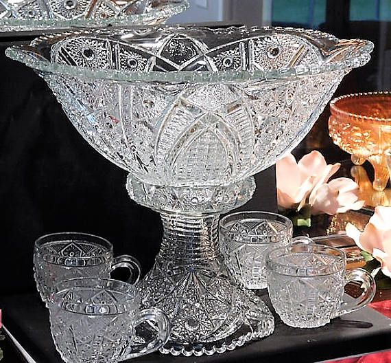 ITEM #RA-145 (Box R-8) A stunning EAPG punch bowl and stand with 4 matching cups produced by the Indiana Glass Co in the 1890s. The pattern is referred to as Indianas #123, but some collectors refer to it as Panelled Daisies and Finecut.  Bowl measures 12 in diameter and is 5 tall. Weighs 4 lbs 5 oz. Base measures 6 base diameter and is 5 1/2 tall. Weighs 1 lb and 14 oz The cups measure 2 3/4 diameter not measuring to the handle and stand 2 1/3 tall. Each weigh 5 oz.  Condition...