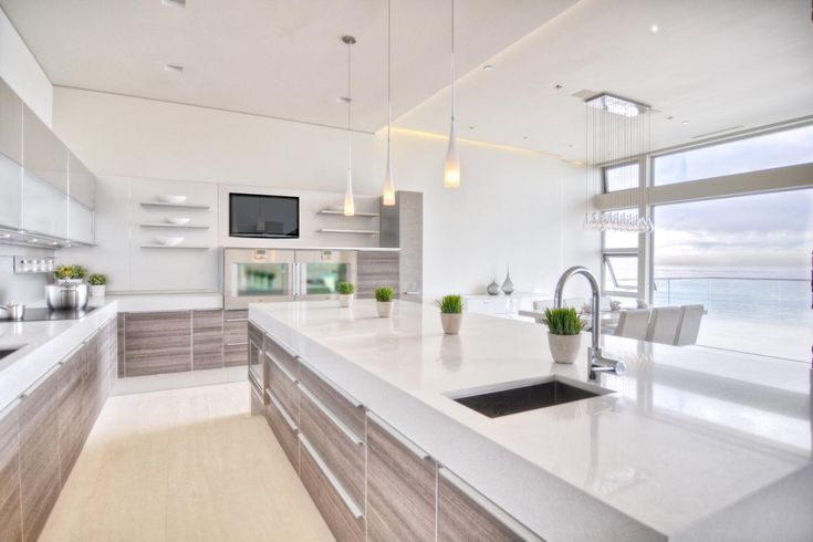 This gorgeous modern kitchen echoes the serene beauty of a white sandy beach, punctuated by the stunning ocean view just beyond the room's enormous windows. Soft gray cabinets bring a touch of textured contrast, but the overall feel is sleek and airy.