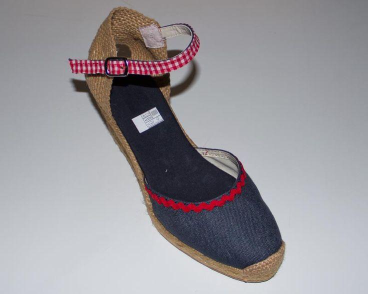 Alpargata cuña alta de pulsera. Color azul marino, con detalle en ondulina y pulsera en vichy rojo, detalle flor en talón. Tallas: 35-41 Precio: 40€