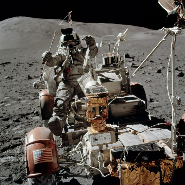 The second of three photos Eugene Cernan took of Jack Schmitt jumping into the LMP Rover seat. Good view of the segmented mirror on the top of the TV camera. Jack has the LRV sampler in his right hand